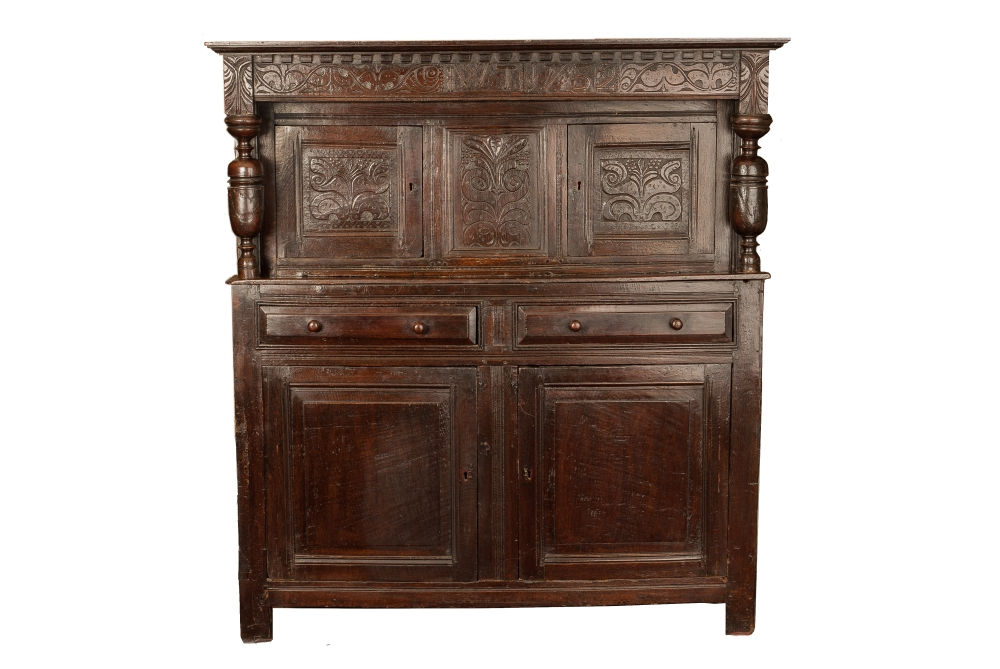 An early 18th Century floral carved and panelled Oak court cupboard